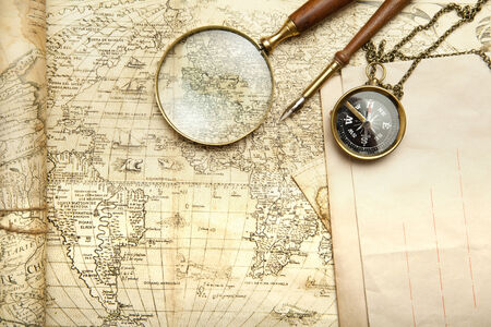 compass, magnifying glass and pen lying on an ancient world map Stock Photo