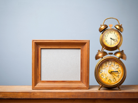 wood tick: Vintage alarm clock on the table with photo frame