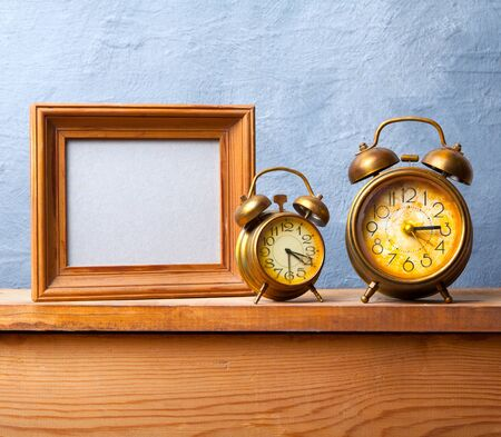 frame wall: Vintage alarm clock on the table with photo frame