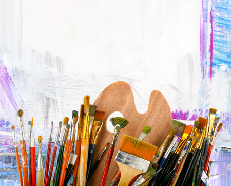 hobbies: Brushes with a palette  on a creative background Stock Photo