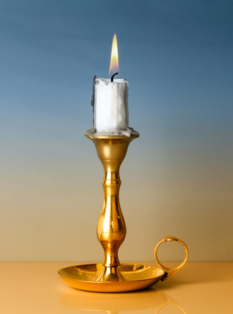 Antique metal candlestick with burning candle