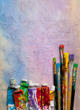 Tubes of  oil paint and artist paintbrushes on palette closeup .