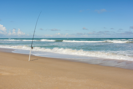 Bright summers day on a deserted south australian beach. Lone fishing road sits in holder with waves crashing in backgorund