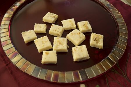 Holiday white chocolate fudge on red mosaic tile plate 스톡 콘텐츠