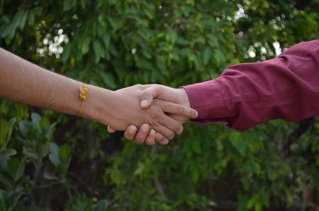 manos estrechadas: Los apretones de manos sobre fondo verde Foto de archivo