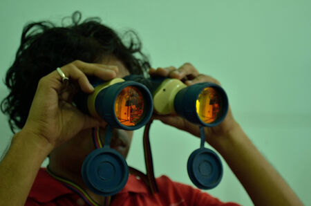 handcarves: Young man searching for success with a binocular