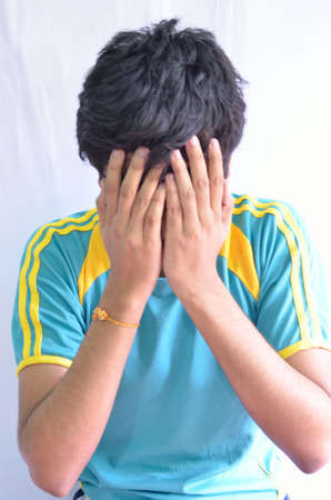 Young man hiding his face with grief photo