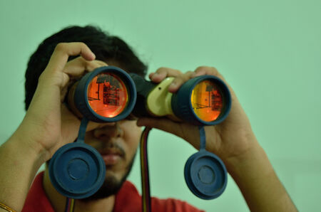searching for: Young man with binocular on eyes searching for success Stock Photo
