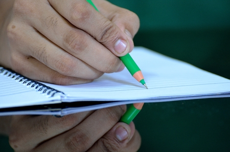 Human hand writing on notebook with a green pen reflected on table photo
