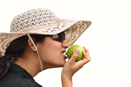 Young woman with big hat eating green fruit photo