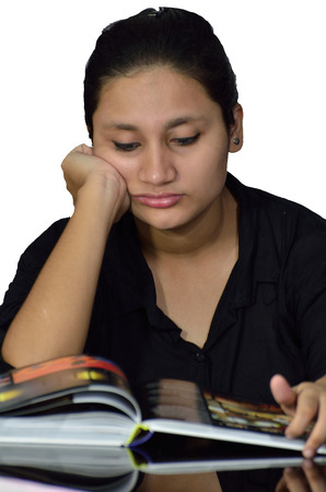 deeply: Young girl reading a book on table and thinking deeply Stock Photo