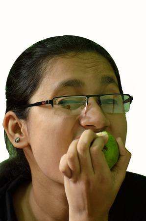 Young woman eating greet fruits photo