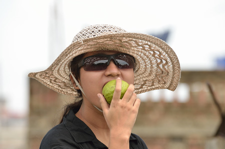 Portrait of young woman with big hat and sunglass eating green fruit photo
