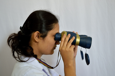 Female doctor looking through binoculars photo