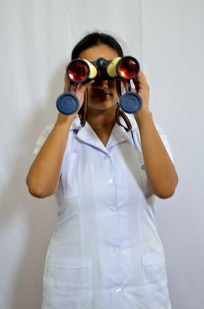 Young nurse looking from binoculars toward camera photo