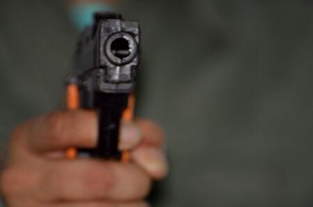 organized crime: Hand holding a gun ina dark.