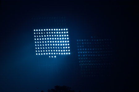 Stadium floodlights against a dark night sky background . photo