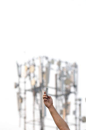 Hand holding a mobile phone next to a communication tower photo
