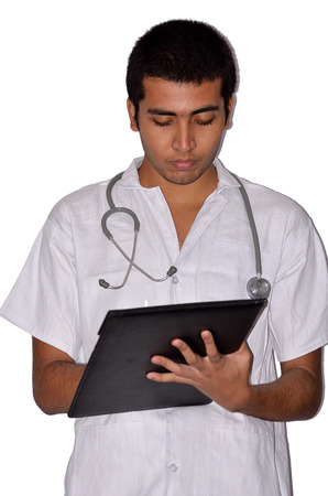 young male doctor: Young male doctor holding a clipboard and writing. Stock Photo