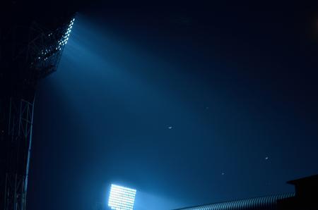 leisure game: Stadium floodlights against a dark night sky background .