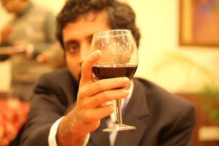 dinner wear: Businessman holding red wine and celebrating a business deal. Stock Photo
