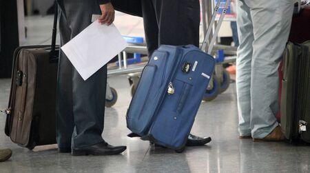 fila de personas: Hombre de pie con malet�n en el aeropuerto. Foto de archivo