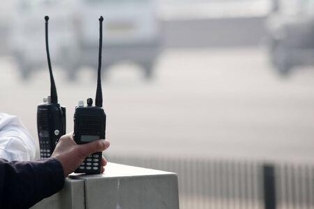 walkie talkie: Security Man holding Walkie-talkie. Stock Photo