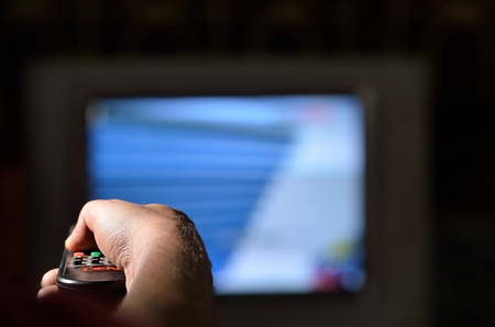 changing channels: Man control television with remote.