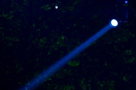 searchlight: Beam of blue light on black . Applied to a searchlight torch.