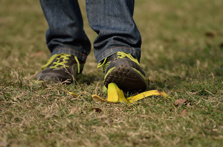 banana skin: Man foot about to slip and fall on a banana skin. Stock Photo