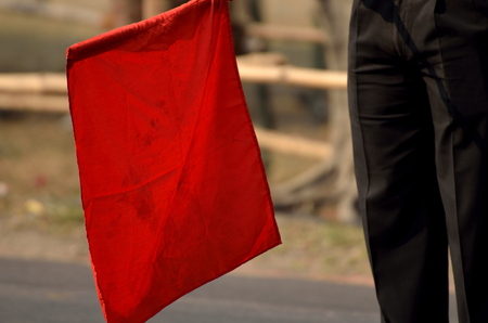 danger symbol: Red flag shown in a road for stop. Stock Photo