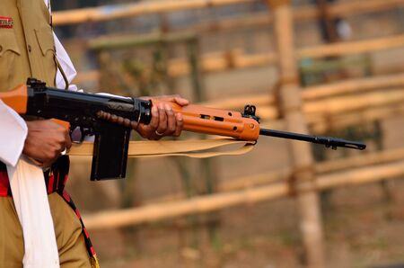 finger on trigger: Indian army man is walking with gun at Calcutta. Stock Photo