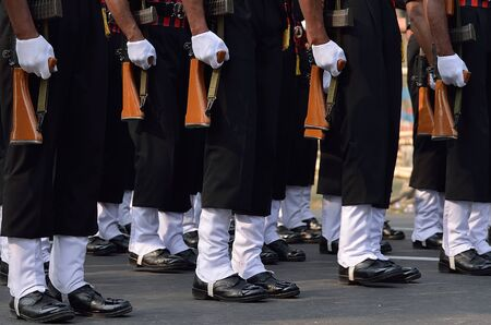 men standing: Indian army men standing with gun