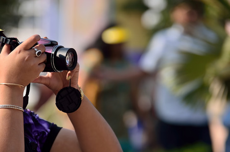 Young girl holding a camera and taking pictures. photo