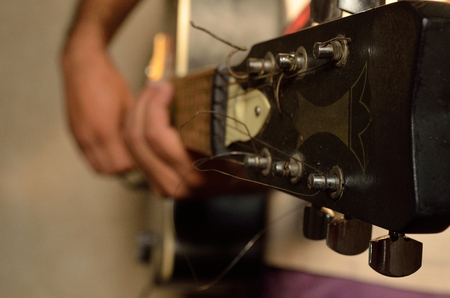 fingerboard: A guitarist playing acoustic guitar.
