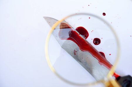 Forensic crime evidence. A bloody knife with fingerprint in white background. photo