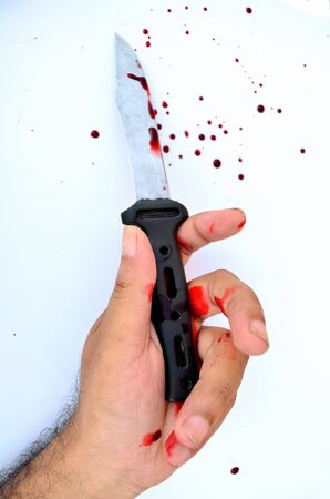 bloodied: A bloodied hand over a bloodied knife in a white background with blood. Stock Photo