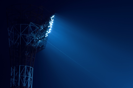 to light: Closeup of stadium floodlights against a dark night sky background