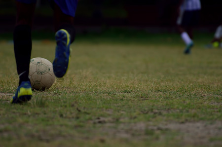 soccer cleats: Boy is playing soccer in a ground. Football in motion is captured. Motion of leg is captured. Stock Photo