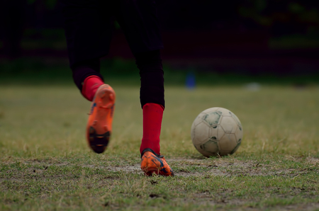 soccer cleats: Boy is playing soccer in a ground.Boy is going to kick a soccer ball