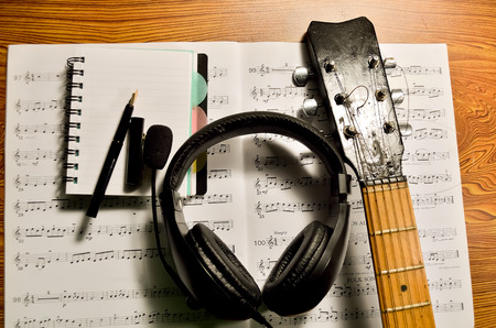 music book: Music book, notepad pen headphone and acoustic guitar on table. Stock Photo