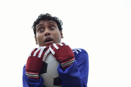 arquero futbol: Portero de fútbol atrapar la pelota en el fondo blanco. Foto de archivo