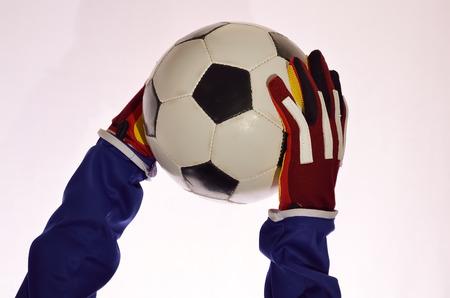 arquero futbol: Portero de fútbol atrapar pelota para salvar a su equipo con las manos en el fondo blanco.