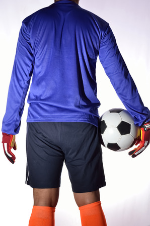 arquero futbol: One soccer player goalkeeper standing with holding ball in white background. Foto de archivo