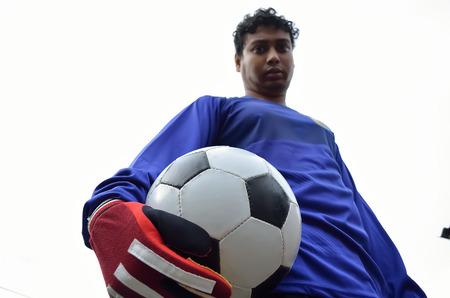 arquero futbol: Portero de fútbol de pie con bola desde un ángulo bajo.