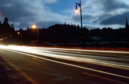 Long exposure, traffic in night running through road.