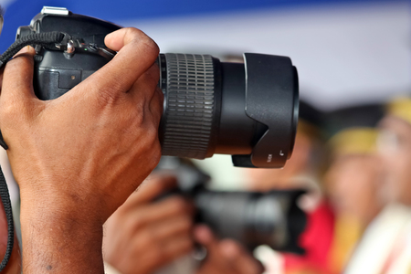 photography: Hand holding DSLR camera for photography Stock Photo