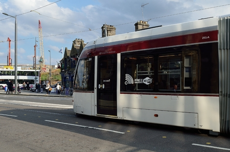 princes street: Edinburgh Tram in Princes Street. The tram is passing by a majestic old fashioned building. Tram is being used as a public transport in Edinburgh.