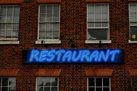 store sign: Glowing neon letter on brick wall saying restaurant. The text restaurant is written using image processing software. It consist 6 layers Stock Photo