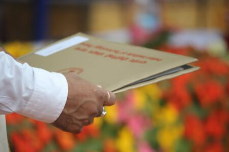 religious clothing: A human hand is offering a degree certificate during a convocation ceremony.